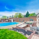 Beautiful pool surrounded by landscaping, [atio, deck and trees